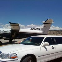 Large white stretch limo parked next to private plane