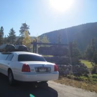 Stagecoach large white stretch limo with cargo boxes parked next to keystone Colorado Ski resort sign