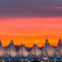 Denver International Airport with orange and purple sunset