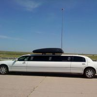 Large white stretch limo parked at small airport