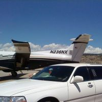 Large stretch white Stagecoach Limo next to private aircraft
